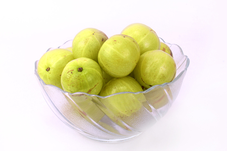 peeled off: green gooseberries in a glass bowl Stock Photo