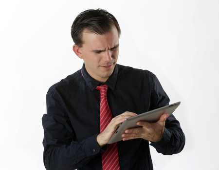 puzzlement: Confused man looking at digital tablet