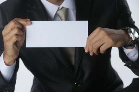 Close up of business man holding white blank card with copyspace ready for your text or letters. Isolated on white background.