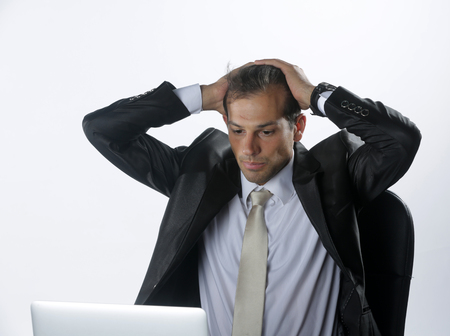 Tired and worried business man at workplace in office holding his head on hands Stock Photo
