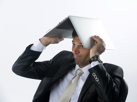 Frustrated and overworked businessman burying his head under a laptop computer  Stock Photo