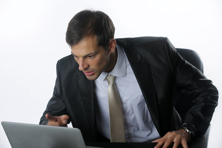 Failed again. Furious young man in shirt and tie looking at computer monitor and shouting while sitting at his working place