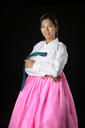 Korean Woman with Hanbok, the traditional Korean dress gesturing open hand with copy space for product or text in white background
