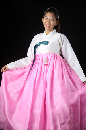 Korean Woman with Hanbok, the traditional Korean dress gesturing open hand with copy space for product or text in white background with clipping path.