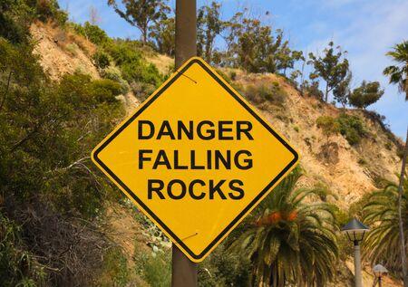 falling rocks Warning sign on a curvy road