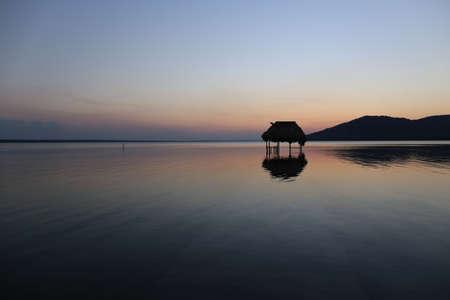 Overwater Hut and Sunset - Lake Peten Itza in Guatemala Stock Photo