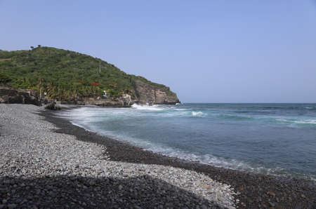 Beautiful turqouise clear sea with black pebble beach at tropical island, Central America