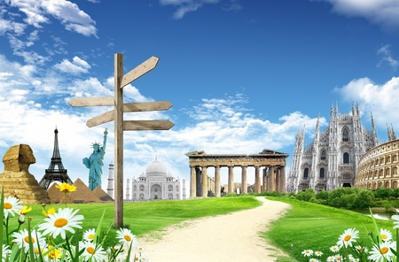 World landmarks with direction panel in he grassland with country road and blue sky and clouds in the background photo