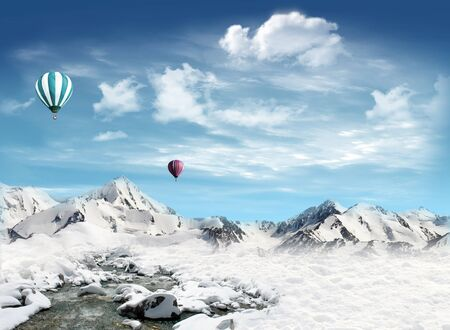 Hot air balloons are flying in the sky over the mountains with snow Imagens