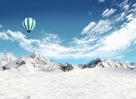Snowfield and mountain landscape with hot air balloon flying in the sky  Stock Photo