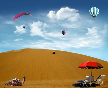 Desert dune with camel and deck chairs with hot air balloon and paragliding flying in the sky photo