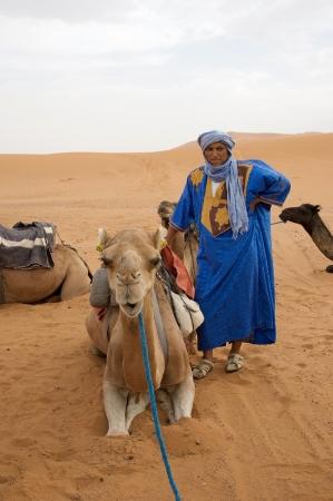 Merzouga, Morocco: berber man and camel among the dunes