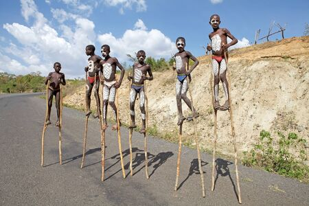 Key Afar, Ethiopia, February 14, 2013: african children of the Banna ethnic group, some of them with tribal paint, show teir performance for the tourist along the road.