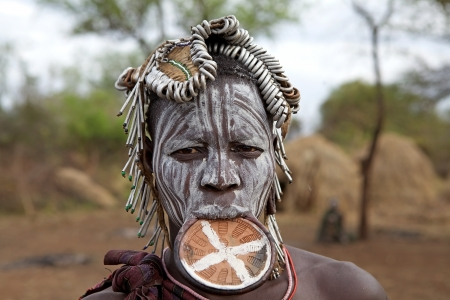 Mago National Park, Ethiopia, February 15, 2013: african woman of the Mursi ethnic group is showing the tribal paint on the face and the plate lips