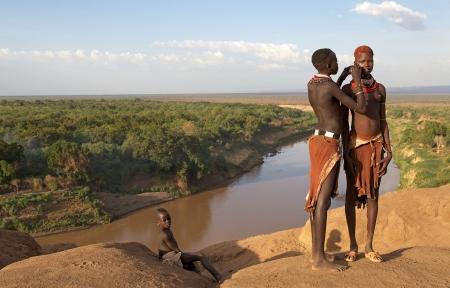 Omo Tal, Karo Dorf, �thiopien, 16. Februar 2013: afrikanische Frauen der Karo ethnischen Gruppe zeigen ihre Stammes-Frisur und Halsketten mit dem Omo Fluss in den Hintergrund. Einer von ihnen macht die Stammes-Farbe auf dem Gesicht des anderen. Editorial