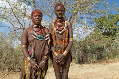 body paint: Kolcho, Ethiopia, February 16, 2013: african tribal women of thge Banna ethnic group, are wearing tribal clothes and necklaces and have tribal body paint and hairstyle along the road to the village
