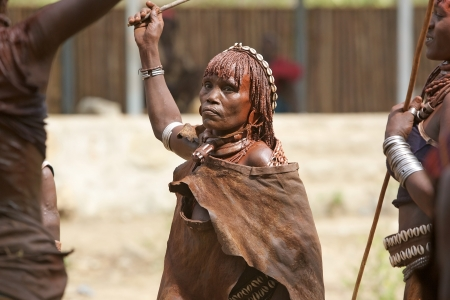 body paint: Turmi, Ethiopia, February 16, 2013: old african woman of the Hamer ethnic group, is showing her tribal hairstyle, necklace of the first wife and body paint at the jumping of the bull ceremony Editorial