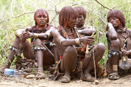 body paint: Turmi, Ethiopia, February 16, 2013: african women of the Hamer ethnic group, are showing their tribal hairstyle and body paint with bells on the legs for dancing at the jumping of the bull ceremony Editorial