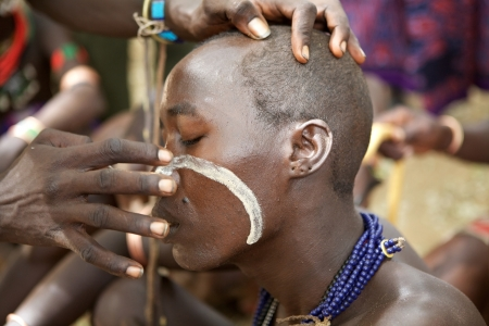 Turmi, Ethiopia, February 16, 2013: african men of the Hamer ethnic group are painting the body to prepare themself for the jumping of the bull ceremony near Turmi, Ethiopia.