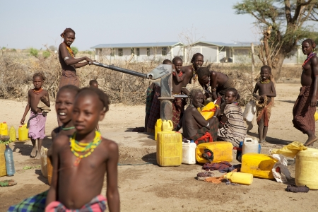 ethiopian: Turmi, Ethiopia, February 17, 2013: african people of the Dasanech or Galeb ethnic group are pumping the water at the water pump in Turmi. Editorial