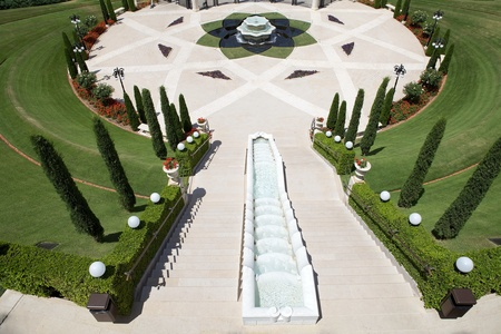 loto: Bahai garden entrance gate at the bottom of the hill with fountain with loto flower shape and pool, Haifa, Israel Stock Photo