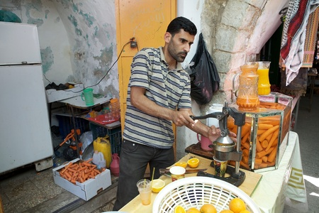 palestinian: Palestinian man is making the orange juice with fresh oranges in the palestinian sector in Hebron, Israel