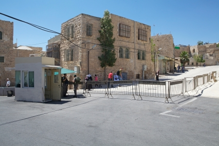 palestinian: Israeli soldiers stand guard at the checkpoint at the border between the israeli territory and palestinian territory in Hebron, Israel  The palestinian people can not pass the barriers, because the situation between isreli colony and arab people is very b Editorial