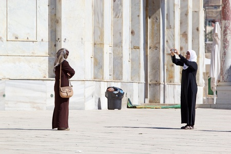 Arab women with traditional dress are visiting the mosque and taking photographs at the Temple Mount, Jerusalem, Israel
