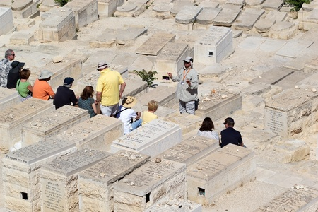 Jewish tourists and pilgrims with the guide are visiting the ancient jewish cemetery on the Mount of Olives, Jerusalem, Israel