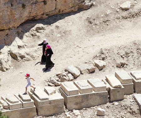 Arab women are walking in the ancient necropolis and jewish cemetery on the Mount of Olives while a child is walking on the tombs, Jerusalem, Israel