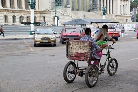 paseo: Havana, Cuba, January 4, 2014  cuban man is driving a bicycle taxi along the Paseo de Prado at the Havana Editorial