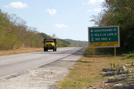 guantanamo: Traffic sign and lorry alont the road to Guantanamo  Guantanamo is a municipality and a city in the Southeast of Cuba and capital of the Guantanamo province  About 15 km outside the town lies Guantanamo Bay, a natural harbour wich has been military occupi