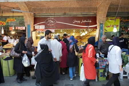 Iranian people are byiing and selling food at the bazaar, the old traditional market, along the streets in Tehran, Iran Editorial