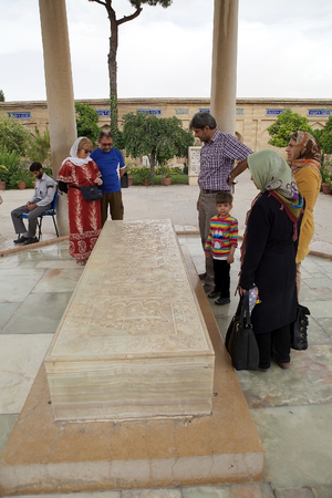 peo: Iranian people and tourists near the tomb of Hafez at the Memorial of Hafez, Shiraz, Iran  Hafez was one of the major persian poets of the medieval period  He was born in Shiraz in 1315 and died there in 1390  This is a place of pilgrimage for iranian peo Editorial