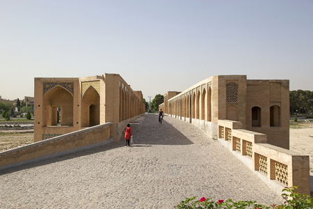 safavid: Iranian people are crossing the Khaju Bridge at Isfahan, Iran  Khaju Bridge was built by the persian Safavid King Shah Abbas II around 1650, serving as both a bridge and a dam across the Zayandeh river, now dry in town  Khaju Bridge has 24 arches and is 1 Editorial