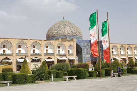 safavid: Iranian flags and Sheik Lotfollah Mosque at the Naqsh-e Jahan square, Isfahan, Iran. The mosque is one of the architectural masterpieces of Safavid iranian architecture. The costraction started in 1603 and was finished in 1619. Editorial