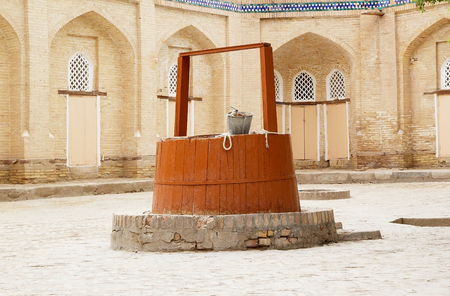 water well: Courtyard and water well at the Islam Khoja Complex at the Itchan Kala, Khiva, Uzbekistan.  Stock Photo