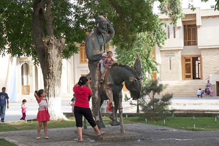 populist: Tourists at the Nasreddin Hodja monument in the historic centre of Bukhara, Uzbekistan. Nasreddin was a seljucq satirical sufi, believed to have lived and died during the 13th century. He is considered a populist philosopher and wise man. Bukhara is a cit
