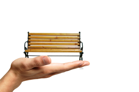 Classic garden bench on the human hand on the isolated background