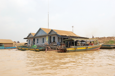 sap: Traditional floating house and boat on the Tonle Sap lake, Cambodia. Tonle Sap is a combined lake and river system of major Importance to Cambodia and it is the largest freshwater lake in the Southeast Asia