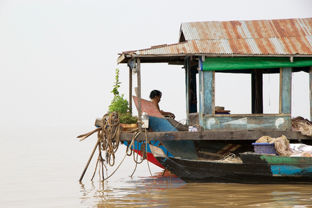tonle sap: Inhabitant of the traditional floating house and boat on the Tonle Sap lake, Cambodia. Tonle Sap is a combined lake and river system of major importance to Cambodia and it is the largest freshwater lake in the Southeast Asia Editorial