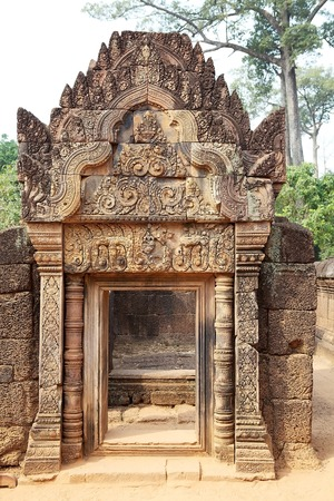 hindu god shiva: The intricate reliefs carving of red colored stone at the Banteay Srei temple, located in the area of Angkor,Siem Reap, Cambodia. Banteay Srei temple is a 10th century temple dedicated to the Hindu God Shiva. It is built largely of red sandstone with elab Stock Photo