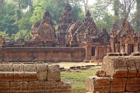 largely: Banteay Srei temple ruins, located in the area of Angkor,Siem Reap, Cambodia. Banteay Srei temple is a 10th century temple dedicated to the Hindu God Shiva. It is built largely of red sandstone with elaborate decorative wall carving.