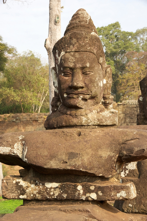 enduring: A deva faces on le left side of the causeway that spans the moat in front of Angkor Thom South gate, Siem Reap, Cambodia.  Angkor Thom was the last and most enduring capital of Khmer Empire and covers an area of 9 Kmsq within which are located several mon