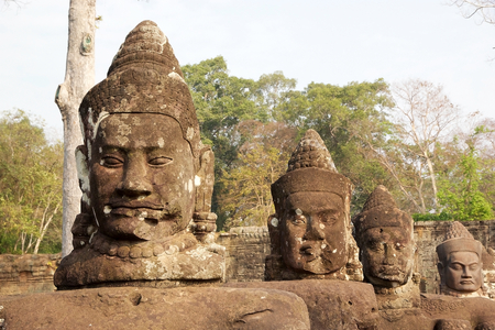 sev: A row of devas faces on le left side of the causeway that spans the moat in front of Angkor Thom South gate, Siem Reap, Cambodia.  Angkor Thom was the last and most enduring capital of Khmer Empire and covers an area of 9 Kmsq within which are located sev Stock Photo