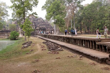 two and two thirds: Tourists are walking along the sandstone causeway to Baphuon temple, located in Angkor Thom, northwest of Bayon, Angkor, Siem Reap, Cambodia. The causeway is about 200 m long. About two thirds of the way along the causaway a badly ruined cruciform pavilli