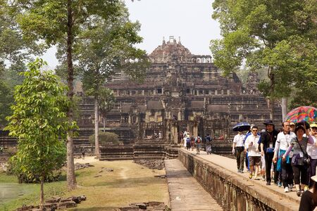 two and two thirds: Tourists are walking along the sandstone causeway to and from Baphuon temple, located in Angkor Thom, northwest of Bayon, Angkor, Siem Reap, Cambodia. The causeway is about 200 m long. About two thirds of the way along the causaway a badly ruined crucifor