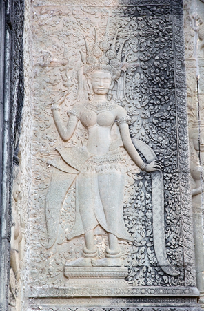 Hindu deity bas-relief at Angkor Wat, Angkor, Siem Reap, Cambodia. Angkor Wat was first a Hindu later a Buddhist temple complex and the largest religious monument in the world. It was built in the first half of 12th century by the Khmer King Suryavarman i photo