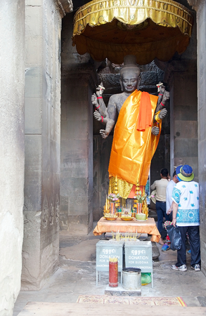 The statue of Vishnu under the southern tower along the external enclosure at Angkor Wat, Angkor, Siem Reap, Cambodia. Angkor Wat was first a Hindu later a Buddhist temple complex and the largest religious monument in the world.