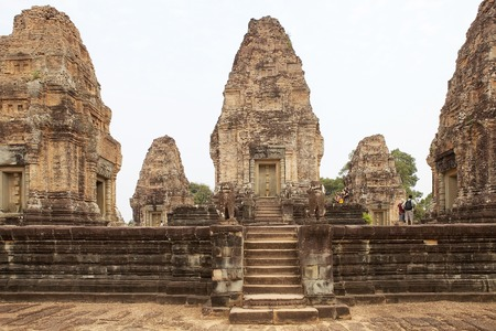 enclosing: Tourists are visiting the East Mebon temple ruins, Angkor, Siem Reap, Cambodia. East Mebon temple was built in the second half of 10th century. Built in the general style of Pre Rup, East Mebon has two enclosing and three tiers. Stock Photo